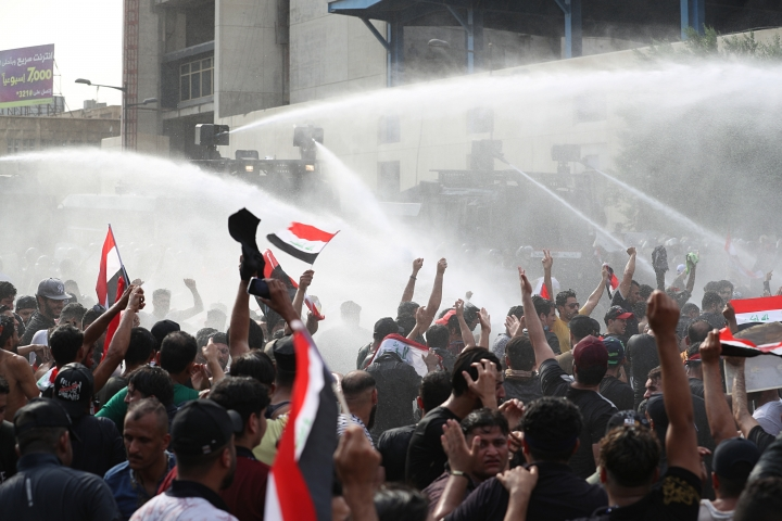 Iraqi security forces use a water cannon during a protest in Tahrir Square, in central Baghdad, Iraq, Tuesday, Oct. 1, 2019. Iraqi security forces fired tear gas on hundreds of protesters in the Iraqi capital who were demonstrating against corruption and bad public services. (AP Photo/Khalid Mohammed)