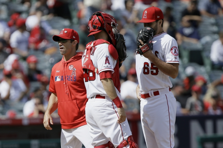 Los Angeles Angels manager Brad Ausmus, left, walks away after switching in relief pitcher Jake Jewell, right, who talks with catcher Anthony Bemboom, center, during the fourth inning of a baseball game against the Houston Astros in Anaheim, Calif., Sunday, Sept. 29, 2019. (AP Photo/Alex Gallardo)