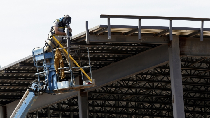 This July 1, 2019, photo shows a construction worker atop a new building in Hillsborough, N.C. On Tuesday, Oct. 1, the Commerce Department reports on U.S. construction spending in August. (AP Photo/Gerry Broome)