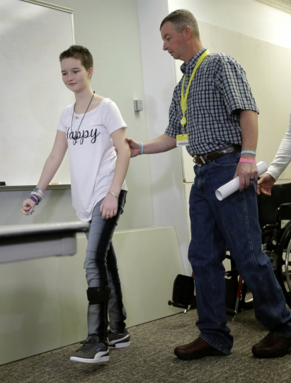 FILE - In this April 20, 2017, file photo, Matt Turner aids his daughter Deserae Turner, as they arrive for a news conference at Primary Children's Hospital, in Salt Lake City. Turner, a Utah high school student who survived a gunshot wound to the head was named homecoming queen by her classmates. Turner was found in a ditch after being shot in the back of the head and left for dead by two classmates in February 2017. (AP Photo/Rick Bowmer, File)