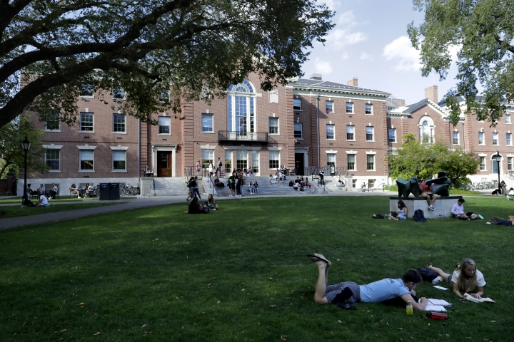 In this Sept. 25, 2019, photo, people rest on grass while reading at Brown University in Providence, R.I. Tax and charity records show that prestigious universities around the world, including Brown, have accepted at least $60 million from the family that owns OxyContin maker Purdue Pharma over the past five years, even as the company has been embroiled in lawsuits over its role in the opioid epidemic. (AP Photo/Steven Senne)