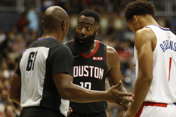 Houston Rockets shooting guard James Harden (13), center, reacts to a referee's call against him during the third quarter of an NBA preseason basketball game against the Los Angeles Clippers, Thursday, Oct 3, 2019, in Honolulu. (AP Photo/Marco Garcia)