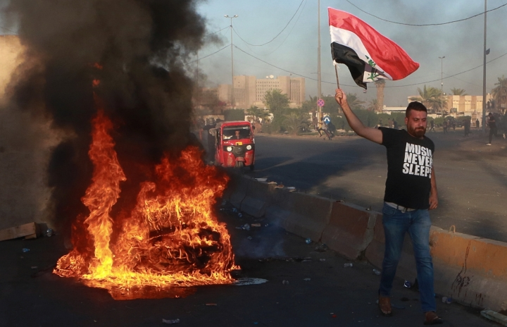 """Anti-government protesters set fires and close a street during a demonstration in Baghdad, Iraq, Friday, Oct. 4, 2019. Security forces opened fire directly at hundreds of anti-government demonstrators in central Baghdad, killing some protesters and injuring dozens, hours after Iraq's top Shiite cleric warned both sides to end four days of violence """"before it's too late."""" (AP Photo/Khalid Mohammed)"""