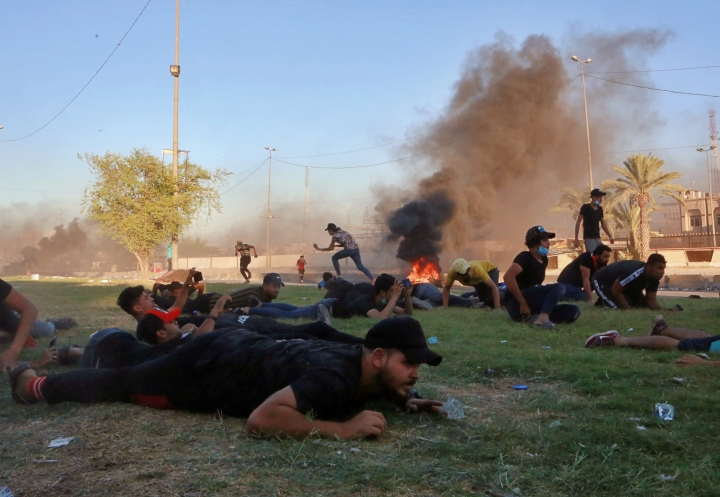 """Anti-government protesters take cover while Iraq security forces fire during a demonstration in Baghdad, Iraq, Friday, Oct. 4, 2019. Security forces opened fire directly at hundreds of anti-government demonstrators in central Baghdad, killing several protesters and injuring dozens, hours after Iraq's top Shiite cleric warned both sides to end four days of violence """"before it's too late."""" (AP Photo/Khalid Mohammed)"""