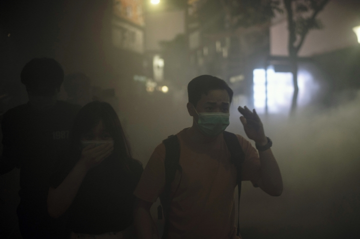 A man and woman walks through smoke from a fire near a subway station entrance in Hong Kong on Friday, Oct. 4, 2019. Masked protesters streamed into Hong Kong streets Friday after the city's embattled leader invoked rarely used emergency powers to ban masks at rallies in a hardening of the government's stance after four months of anti-government demonstrations. (AP Photo/Felipe Dana)