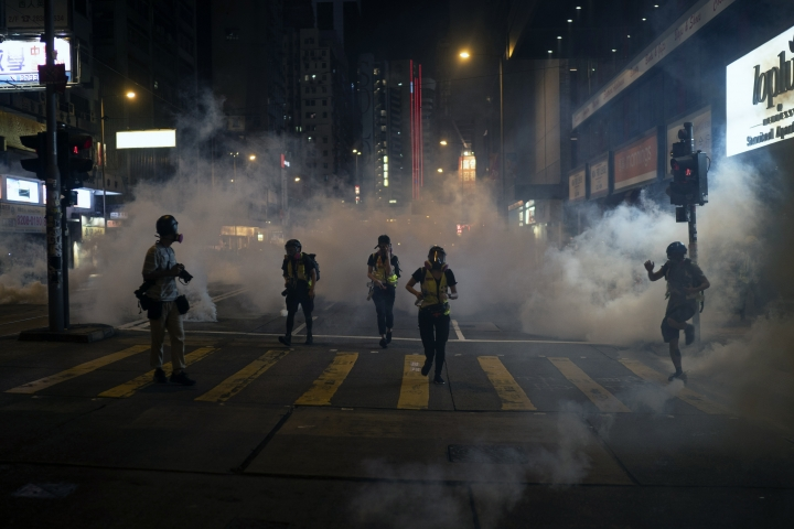 Emergency responders and journalists run from tear gas during a protest in Hong Kong on Friday, Oct. 4, 2019. Masked protesters streamed into Hong Kong streets Friday after the city's embattled leader invoked rarely used emergency powers to ban masks at rallies in a hardening of the government's stance after four months of anti-government demonstrations. (AP Photo/Felipe Dana)