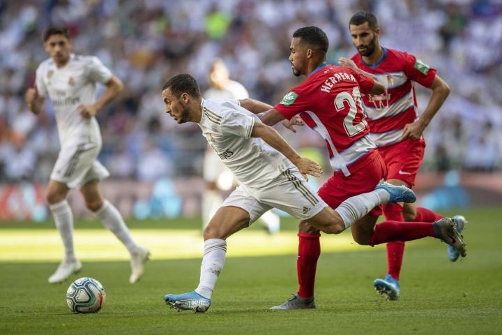 Real Madrid's Eden Hazard runs with the ball against Granada's Yangel Herrera during the Spanish La Liga soccer match between Real Madrid and Granada at the Santiago Bernarbeu stadium in Madrid, Saturday, Oct. 5, 2019. (AP Photo/Bernat Armangue)