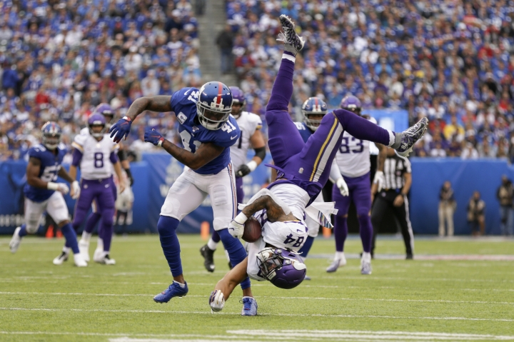 Minnesota Vikings tight end Irv Smith (84) makes a catch as he flips over New York Giants free safety Antoine Bethea (41) during the second quarter of an NFL football game, Sunday, Oct. 6, 2019, in East Rutherford, N.J. (AP Photo/Adam Hunger)