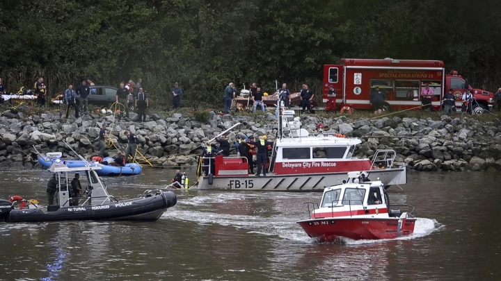 Emergency personnel, including divers, work on the Chesapeake & Delaware Canal where a vehicle plunged into the water from South Canal Road, west of St. Georges, Del., Sunday, Oct. 6, 2019. (William Bretzger/The News Journal via AP)