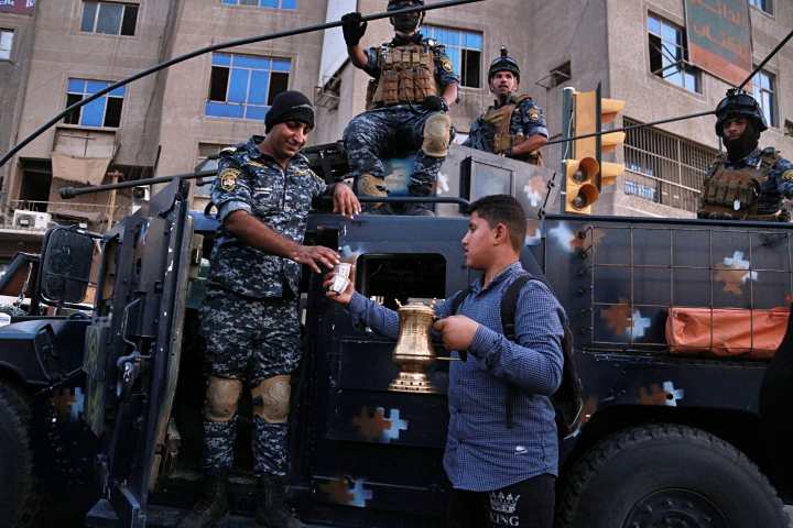 A street vendor sells coffee to the Iraqi Federal police as they deployed in Sadr City, Baghdad, Iraq, Monday, Oct. 7, 2019. Iraq's prime minister on Monday ordered the police to replace the army in Sadr City, a heavily populated Shiite neighborhood of Baghdad where dozens of people were killed or wounded in weekend clashes stemming from anti-government protests. (AP Photo/Hadi Mizban)