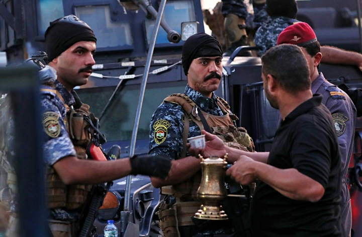 A street vendor sells coffee to members of the Iraqi Federal police as they deployed in Sadr City, Baghdad, Iraq, Monday, Oct. 7, 2019. Iraq's prime minister on Monday ordered the police to replace the army in Sadr City, a heavily populated Shiite neighborhood of Baghdad where dozens of people were killed or wounded in weekend clashes stemming from anti-government protests. (AP Photo/Hadi Mizban)