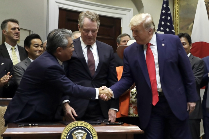 President Donald Trump shakes hands with Japanese Ambassador to the United States Shinsuke Sugiyama, left, and U.S. Trade Representative Robert Lighthizer after they signed a trade agreement in the Roosevelt Room of the White House, Monday, Oct. 7, 2019, in Washington. (AP Photo/Evan Vucci)