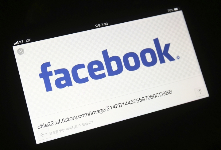 FILE - This Wednesday, March 21, 2018, file photo shows the Facebook logo on a smartphone in Ilsan, South Korea. Facebook has agreed to pay $40 million to advertisers who said it inflated the amount of time its users watched videos. (AP Photo/Ahn Young-joon, File)