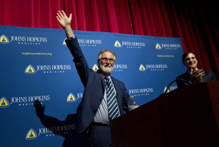 Professor Gregg Semenza, accompanied by Johns Hopkins University President Ron Daniels, waves to the crowd during a news conference after he was awarded the 2019 Nobel Prize in Medicine at Johns Hopkins Medicine Hospital in Baltimore, Md., Monday, Oct. 7, 2019. The 2019 Nobel Prize in Medicine has been jointly awarded to William Kaelin Jr., Sir Peter Ratcliffe and Gregg Semenza for their pioneering research into how human cells respond to changing oxygen levels. (AP Photo/Jose Luis Magana)