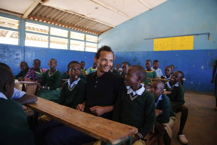 Gerald Erebon sits with students at his old primary school where he said kids used to be tease him about him being the priest's son, in the Isiolo area of the Archers Post settlement in Kenya on Sunday, June 30, 2019. The Vatican is investigating Erebon's claim that his father is the Rev. Mario Lacchin, an Italian missionary priest who impregnated his mother soon after she turned 16. (AP Photo/Brian Inganga)