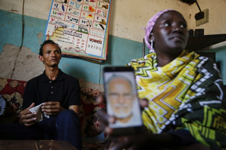 "Gerald Erebon sits with his aunt, Scolastica Apayo, as she holds a phone displaying a photo of the Rev. Mario Lacchin, during an interview at her home in the Isiolo area of the Archers Post settlement in Kenya on Sunday, June 30, 2019. Scolastica said her sister, Sabina Losirkale, finally told her the secret in 2012, two weeks before she died. ""Now that my days are over,"" her sister told her, she could reveal all: ""When Gerald will ask you who's his father, just tell him: Father Mario."" (AP Photo/Brian Inganga)"