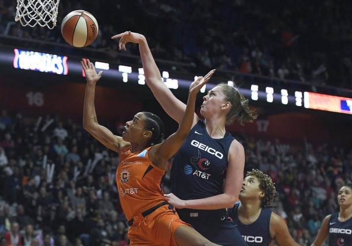 Connecticut Sun's Jasmine Thomas, left, drives to the basket against Washington Mystics' Emma Meesseman during the first half in Game 4 of basketball's WNBA Finals, Tuesday, Oct. 8, 2019, in Uncasville, Conn. (AP Photo/Jessica Hill)