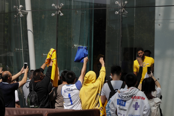 An unidentified LA Lakers player looks at sees fans outside the Ritz-Carlton hotel in Shanghai, China, Thursday, Oct. 10, 2019. NBA Commissioner Adam Silver told the Brooklyn Nets and Los Angeles Lakers on Wednesday that the league is still expecting them to play as scheduled this week, even while the rift between the league and Chinese officials continued in ways that clearly suggested the two planned games in Shanghai and Shenzhen were anything but guaranteed. (AP Photo/Andy Wong)