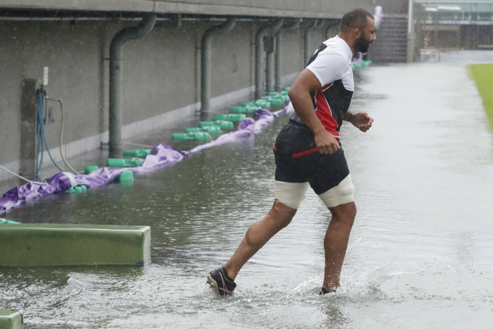 Japan team's Michael Leitch works out, ahead of their Rugby World Cup Pool A match against Scotland as Typhoon Hagibis approaches Saturday, Oct. 12, 2019 in Tokyo. (Kyodo News via AP)