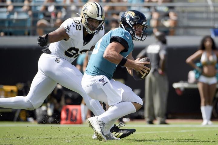 Jacksonville Jaguars quarterback Gardner Minshew, right, tries to scramble past New Orleans Saints defensive end Marcus Davenport (92) during the first half of an NFL football game, Sunday, Oct. 13, 2019, in Jacksonville, Fla. (AP Photo/Phelan M. Ebenhack)