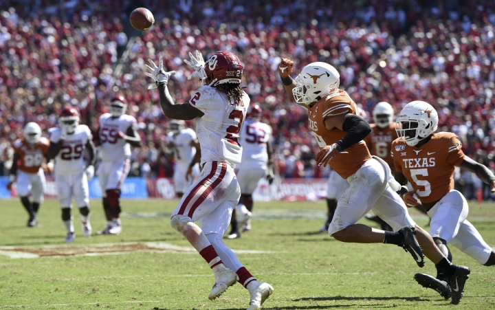 Oklahoma wide receiver CeeDee Lamb (2) hauls in his third touchdown reception in front of Texas defensive back Brandon Jones (19) in the second half of an NCAA college football game at the Cotton Bowl, Saturday, Oct. 12, 2019, in Dallas. Lamb finished with 171 receiving yards and three touchdowns as Oklahoma won 34-27. (AP Photo/Jeffrey McWhorter)