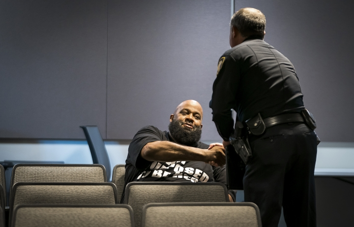 """Fort Worth Police Lt. Brandon O'Neil shakes hands with Roger Foggle after addressing a news conference regarding the shooting of Atatiana Jefferson at the Bob Bolen Public Safety Complex on Sunday, Oct. 13, 2019, in Fort Worth, Texas. A white police officer who killed the black woman inside her Texas home while responding to a neighbor's call about an open front door """"didn't have time to perceive a threat"""" before he opened fire, an attorney for Jefferson's family said. (Smiley N. Pool/The Dallas Morning News via AP)"""