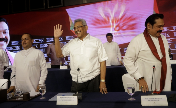 Sri Lankan presidential candidate and former defense chief Gotabaya Rajapaksa, center, waves as he leaves after addressing a news conference in Colombo, Sri Lanka, Tuesday, Oct. 15, 2019. Rajapaksa, who's a front-runner in next month's presidential election says if he wins he won't recognize an agreement the government made with the U.N. human rights council to investigate alleged war crimes during the nation's civil war. (AP Photo/Eranga Jayawardena)