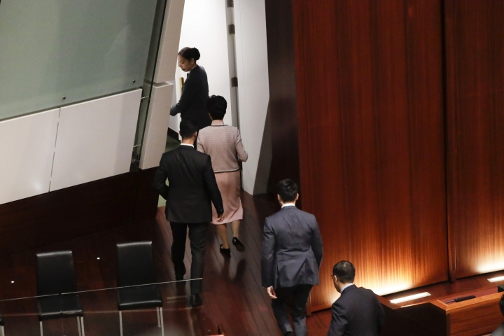 Hong Kong Chief Executive Carrie Lam, second from top, leaves after she was interrupted by pro-democracy lawmakers during her speech at chamber of the Legislative Council in Hong Kong Wednesday, Oct. 16, 2019. Chanting pro-democracy lawmakers have interrupted the start of a speech that Lam was giving laying out her policies. (AP Photo/Mark Schiefelbein)