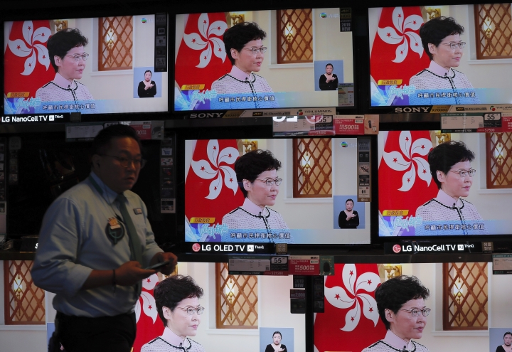 A shopper walks near televisions broadcasting live of Hong Kong Chief Executive Carrie Lam's speech in Hong Kong, on Wednesday, Oct. 16, 2019. In chaotic scenes, furious pro-democracy lawmakers twice forced Hong Kong's leader to stop delivering a speech laying out her policy objectives and then clamored for her to resign after she walked out of the legislature on Wednesday. (AP Photo/Kin Cheung)