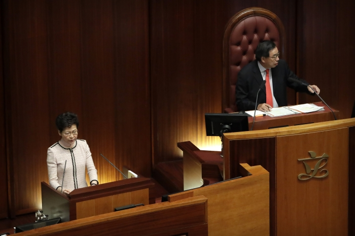 Andrew Leung, right, the President of the Legislative Council, gestures to pan-democratic legislators protesting as Hong Kong Chief Executive Carrie Lam attempts to give a policy speech at the Legislative Council in Hong Kong, Wednesday, Oct. 16, 2019. In chaotic scenes, furious pro-democracy lawmakers twice forced Hong Kong's leader to stop delivering a speech laying out her policy objectives and clamored for her to resign after she walked out of the legislature on Wednesday and then delivered the annual address 75 minutes late via television. (AP Photo/Mark Schiefelbein)