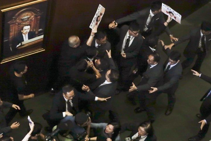 Two pro-democracy lawmakers, with a placard, are escorted out as they shout a slogan while Hong Kong Chief Executive Carrie Lam delivers a speech at chamber of the Legislative Council in Hong Kong Wednesday, Oct. 16, 2019. Chanting pro-democracy lawmakers have interrupted the start of a speech that Lam was giving laying out her policies. (AP Photo/Mark Schiefelbein)