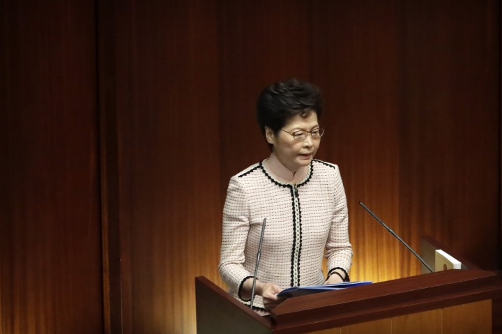 Hong Kong Chief Executive Carrie Lam gives a policy speech at the Legislative Council in Hong Kong, Wednesday, Oct. 16, 2019. In chaotic scenes, furious pro-democracy lawmakers twice forced Hong Kong's leader to stop delivering a speech laying out her policy objectives and clamored for her to resign after she walked out of the legislature on Wednesday and then delivered the annual address 75 minutes late via television. (AP Photo/Mark Schiefelbein)