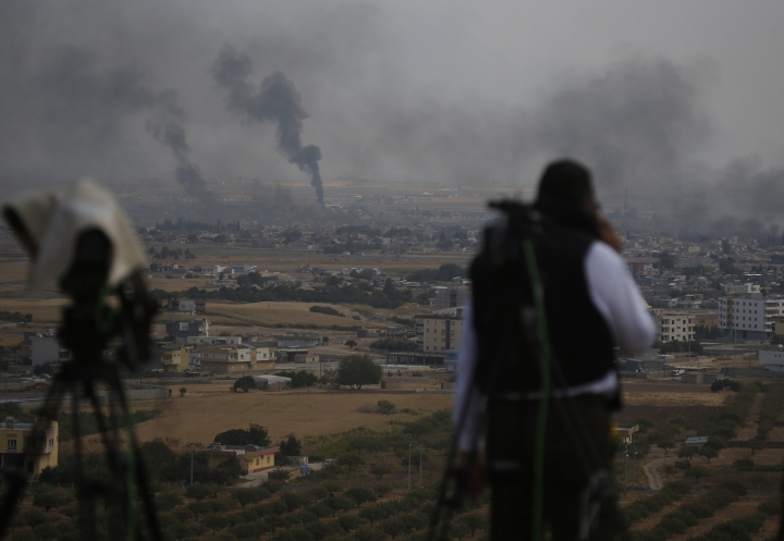 A news cameraman works on a hilltop in Ceylanpinar, Sanliurfa province, southeastern Turkey, as in the background smoke billows from targets in Ras al-Ayn, Syria, during bombardment by Turkish forces, Wednesday, Oct. 16, 2019. Turkey's President Recep Tayyip Erdogan called Wednesday on Syrian Kurdish fighters to leave a designated border area in northeast Syria 'as of tonight' for Turkey to stop its military offensive, defying pressure on him to call a ceasefire and halt its incursion into Syria, now into its eighth day.(AP Photo/Lefteris Pitarakis)