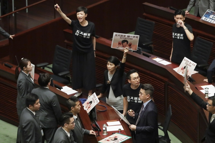 Pro-democracy lawmakers protest as Hong Kong Chief Executive Carrie Lam delivers a speech at chamber of the Legislative Council in Hong Kong Wednesday, Oct. 16, 2019. Chanting pro-democracy lawmakers have interrupted the start of a speech that Lam was giving laying out her policies. (AP Photo/Mark Schiefelbein)