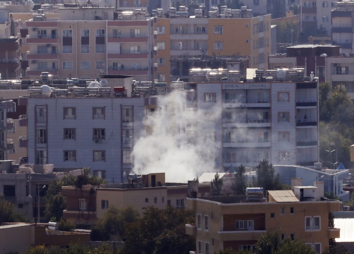 In this photo taken from the Turkish side of the border between Turkey and Syria, in Ceylanpinar, Sanliurfa province, southeastern Turkey, smoke billows from targets in Ras al-Ayn, Syria, caused by shelling by Turkish forces, Friday, Oct. 18, 2019. Fighting continued in a northeast Syrian border town at the center of the fight between Turkey and Kurdish forces early Friday, despite a U.S.-brokered cease-fire that went into effect overnight. Shelling and gunfire could be heard in and around Ras al-Ayn, as smoke billowed from locations near the border with Turkey and the Turkish town of Ceylanpinar. (AP Photo/Lefteris Pitarakis)