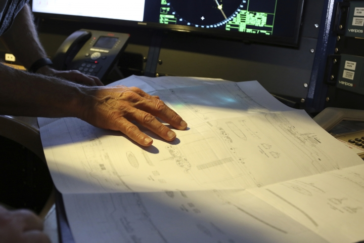 In this Wednesday, Oct. 16, 2019 photo, Vulcan Inc. director of subsea operations of the Petrel, Rob Kraft, left, looks at a blueprint for the Japanese aircraft carrier Kaga, off Midway Atoll in the Northwestern Hawaiian Islands. Weeks of grid searches around the Northwestern Hawaiian Islands have already led the crew of the Petrel to one sunken battleship, the Japanese ship the Kaga. This week, the crew is deploying equipment to investigate what could be another. (AP Photo/Caleb Jones)