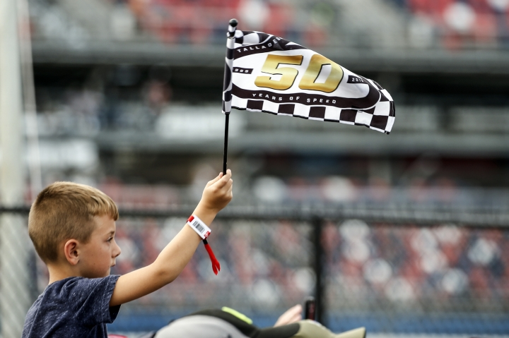 A young fan waves a flag as he watches the celebration in Victory Lane after a NASCAR Cup Series auto race at Talladega Superspeedway, Monday, Oct 14, 2019, in Talladega, Ala. (AP Photo/Butch Dill)