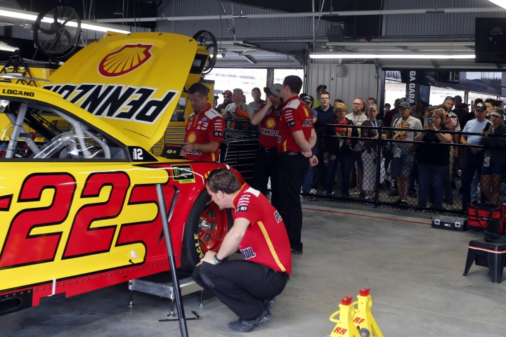 Fans watch the crew for Joey Logano in the new garage facilities during practice for the NASCAR Cup Series auto race at Talladega Superspeedway, Saturday, Oct 12, 2019, in Talladega, Ala. (AP Photo/Butch Dill)
