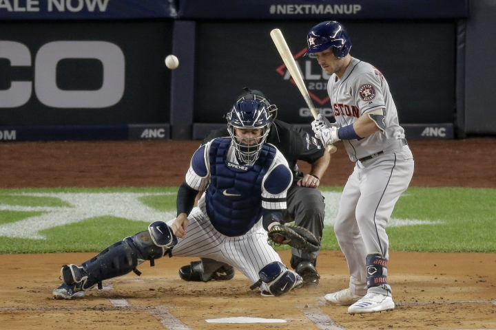 A wild pitch bounces away from New York Yankees catcher Gary Sanchez as Houston Astros' Michael Brantley looks on during the first inning of Game 5 of baseball's American League Championship Series, Friday, Oct. 18, 2019, in New York. George Springer scored on the play. (AP Photo/Seth Wenig)