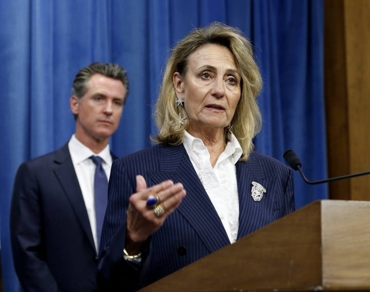 "FILE - In this July 23, 2019, file photo, Marybel Batjer, of the California Public Utilities Commission, speaks during a news conference as Gov. Gavin Newsom looks on in Sacramento, Calif. California's utility regulator is issuing a series of sanctions against Pacific Gas and Electric for what it calls ""failures in execution"" during the largest planned power shut-off in state history to avoid wildfires. Batjer said Monday, Oct. 14, 2019, the utility needs to have a goal of restoring power within 12 hours instead of its current 48 hours, minimize the scale of future outages and better communicate with the public and local officials. (AP Photo/Rich Pedroncelli, File)"