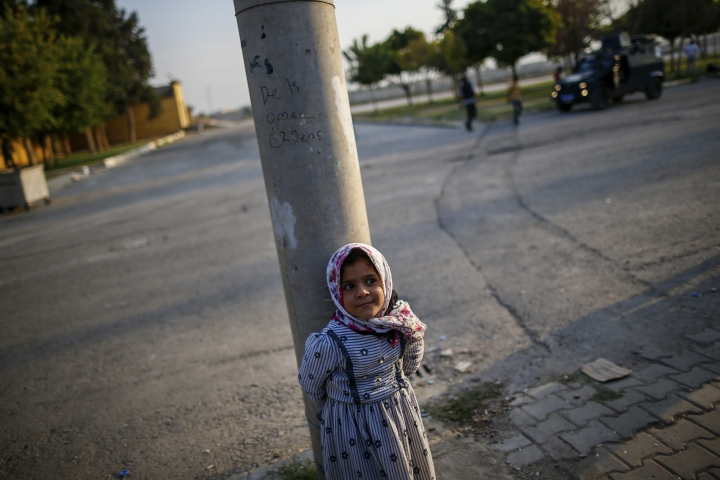 A child stands near the border crossing with Syria, in the border town of Akcakale, Sanliurfa province, southeastern Turkey, Friday, Oct. 18, 2019. The cease-fire in northern Syria got off to a rocky start Friday, as Kurdish leaders accused Turkey of violating the accord with continued fighting at a key border town while casting doubt on provisions in the U.S.-brokered deal with Ankara. (AP Photo/Emrah Gurel)