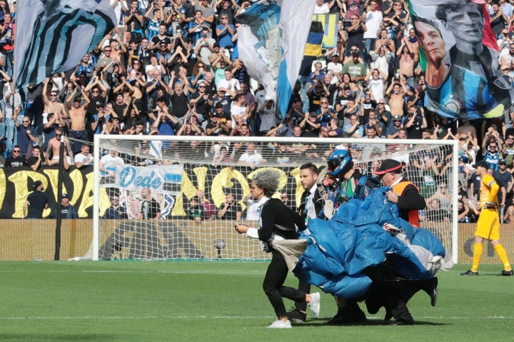 A parachutist who landed on the pitch during a Serie A soccer match between Sassuolo and Inter Milan is taken away after briefly disrupting the match at Mapei Stadium in Reggio Emilia, Italy, Sunday, Oct. 20, 2019. The intrusion came just before Romelu Lukaku was to take a penalty for the visitors. (Elisabetta Baracchi/ANSA via AP)