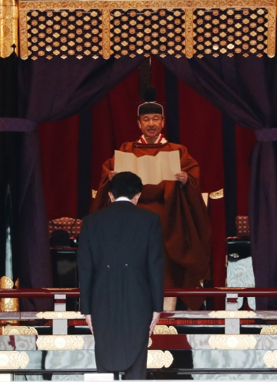 Japan's Emperor Naruhito speaks as Prime Minister Shinzo Abe is seen during a ceremony to proclaim his enthronement to the world, called Sokuirei-Seiden-no-gi, at the Imperial Palace in Tokyo, Japan, Tuesday, Oct. 22, 2019. (Issei Kato/Pool Photo via AP)