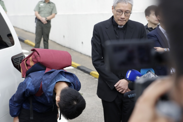 Chan Tong-kai, left, bows after talking to the media as he is released from prison in Hong Kong Wednesday, Oct. 23, 2019. Chan, who's wanted for killing his girlfriend last year on the self-ruled island, had asked the Hong Kong government for help turning himself in to Taiwan after his sentence for money laundering offenses ends on Wednesday. (AP Photo/Mark Schiefelbein)