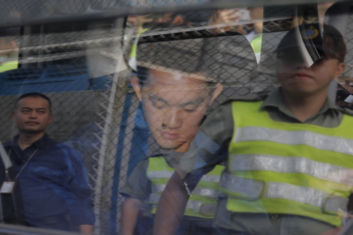 Chan Tong-kai, center, is seen as a prison guard reflected on a car window after Chan was released from prison in Hong Kong Wednesday, Oct. 23, 2019. Chan, who's wanted for killing his girlfriend last year on the self-ruled island, had asked the Hong Kong government for help turning himself in to Taiwan after his sentence for money laundering offenses ends on Wednesday. (AP Photo/Kin Cheung)