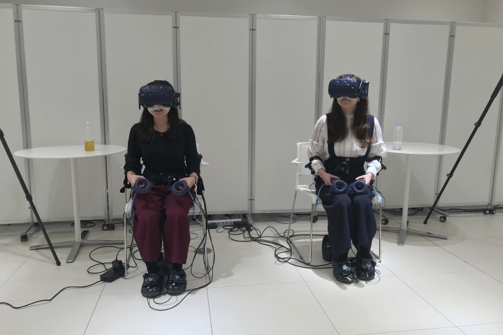"""In this Oct. 18, 2019, photo, people wearing various gadgetry remote control the virtual figures that appear in a car as Nissan demonstrated such technology that is working on at its Oppama test driving course in Yokosuka, near Tokyo. The electric car with smooth four-wheel drive and a virtual friend for the coming age of automated driving are among the technology in development from Nissan. The Japanese automaker is eager to put the scandal over its former star executive Carlos Ghosn behind it. Nissan's newly developed """"all-wheel-control"""" technology delivers a sense of greater control and safety. (AP Photo/Yuri Kageyama)"""