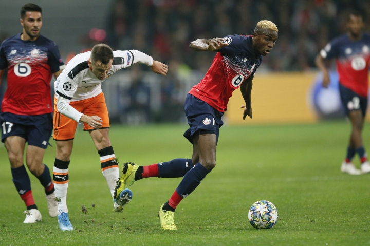 Lille's Victor Osimhen, right, is tackled by Valencia's Denis Cheryshev during the group H Champions League soccer match between Lille and Valencia at the Stade Pierre Mauroy - Villeneuve d'Ascq stadium in Lille, France, Wednesday, Oct. 23, 2019. (AP Photo/Michel Spingler)