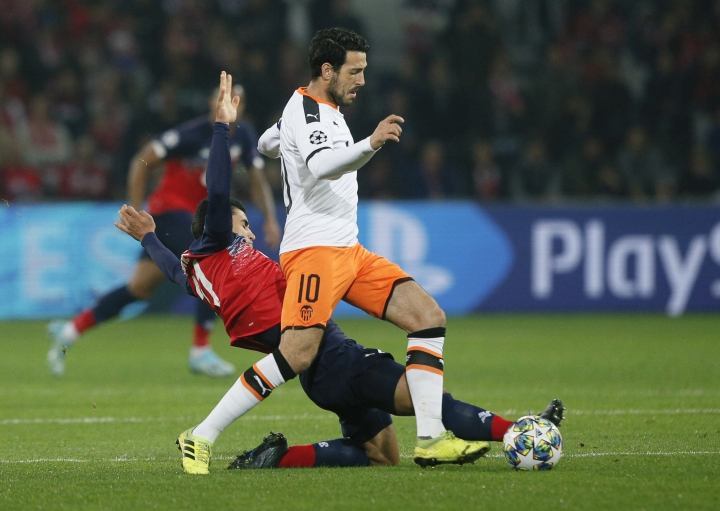 Valencia's Dani Parejo, right, challenges for the ball with Lille's Benjamin Andre during the group H Champions League soccer match between Lille and Valencia at the Stade Pierre Mauroy - Villeneuve d'Ascq stadium in Lille, France, Wednesday, Oct. 23, 2019. (AP Photo/Michel Spingler)