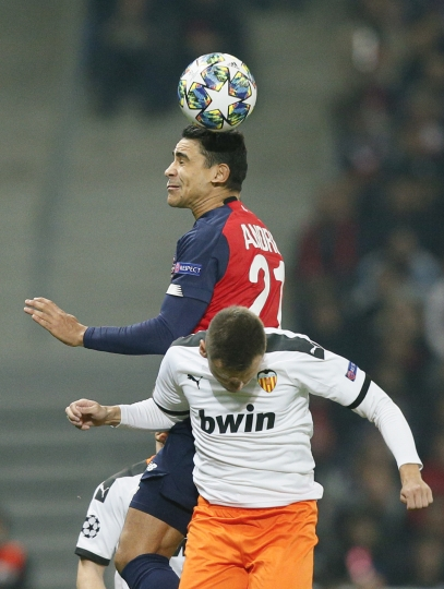 Lille's Benjamin Andre, top, jumps for a header with Valencia's Denis Cheryshev during the group H Champions League soccer match between Lille and Valencia at the Stade Pierre Mauroy - Villeneuve d'Ascq stadium in Lille, France, Wednesday, Oct. 23, 2019. (AP Photo/Michel Spingler)