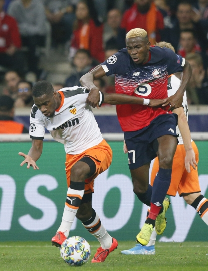 Valencia's Geoffrey Kondogbia, left, challenges for the ball with Lille's Victor Osimhen during the group H Champions League soccer match between Lille and Valencia at the Stade Pierre Mauroy - Villeneuve d'Ascq stadium in Lille, France, Wednesday, Oct. 23, 2019. (AP Photo/Michel Spingler)